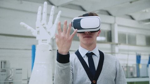 Young scientist manages robotic hand through virtual reality glasses. 4K.