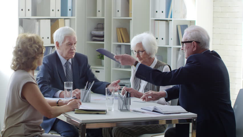 Medium shot of senior businessmen with grey hair sitting at desk in conference room and exchanging handshake, then talking to elderly female transactional lawyers sorting documents