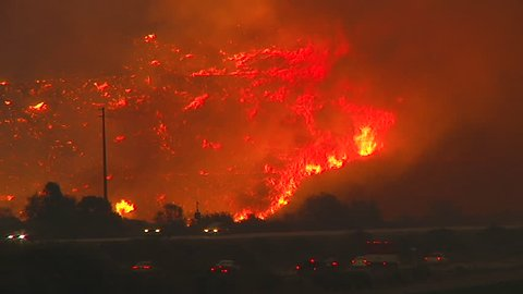 2017 - the Thomas Fire burns at night in the hills above the 101 freeway near Ventura and Santa Barbara, California.