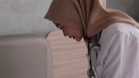 Young asian muslim female doctor making injection to the patient. Edited and raw.