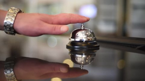 Bell on reception at the hotel to call the administrator. Beautiful blurred background. The hand of the man who presses the call. Close up. Cool concept for hotels. Filmed in July 2018.