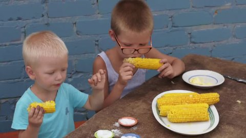 Boys brothers in light clothes eat corn with butter and salt in courtyard of rural house. Children are happy together
