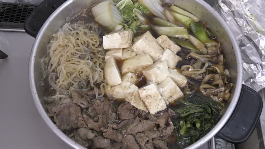 Sukiyaki hot pot during cooking with beef and various ingredients