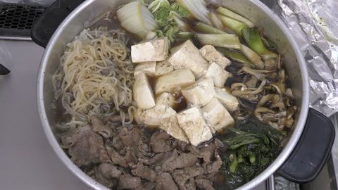 Sukiyaki hot pot during cooking with beef and various ingredients
