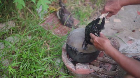 Boiled chicken over burnt red hot charcoal over traditional Asian stove