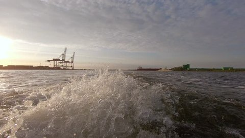 Propellor water close up 4K footage. Tanker and tugboat are sailing in port at the background.