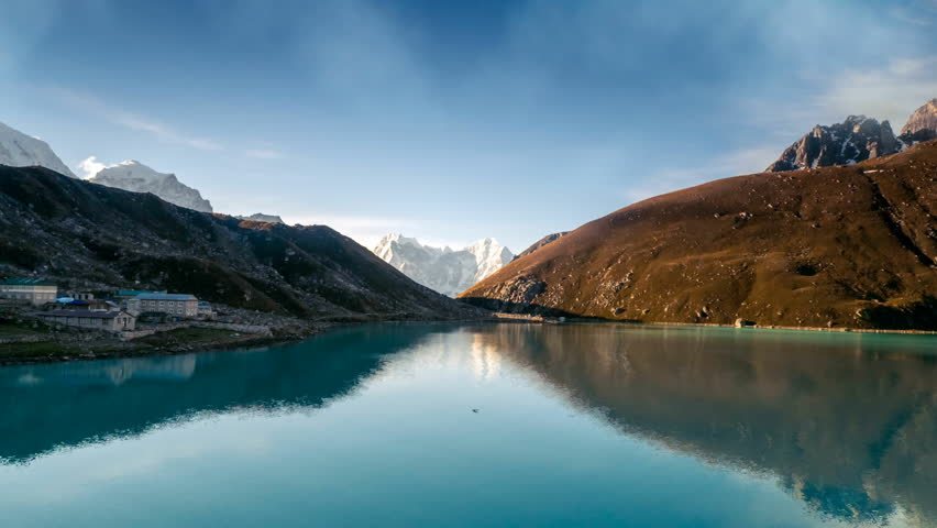 Gokyo Lake, part of Everest Base Camp trek. Sagarmatha National Park, Nepal. Nature landscape. Holidays, travel, recreation. Water waves move and clouds in sky flow. 4K Slow Motion Time Lapse Parallax
