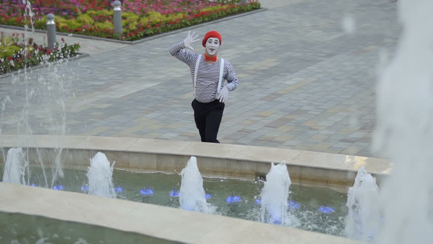 Funny mime touching invisible wall standing near fountains