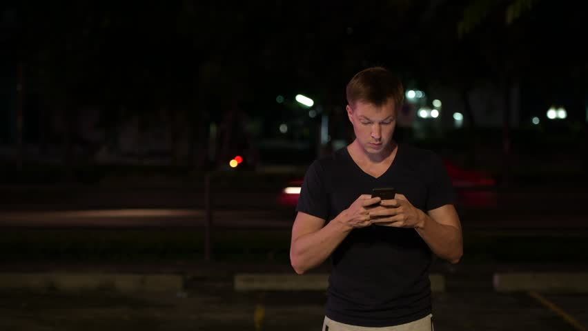 Young handsome Scandinavian man using phone in the streets at night | Shutterstock HD Video #1014153431