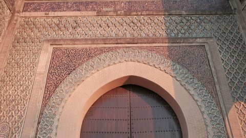 Camera tilt down forward first person POV walking at Bab Mansour Gate wooden door in late afternoon in Meknes, Morocco