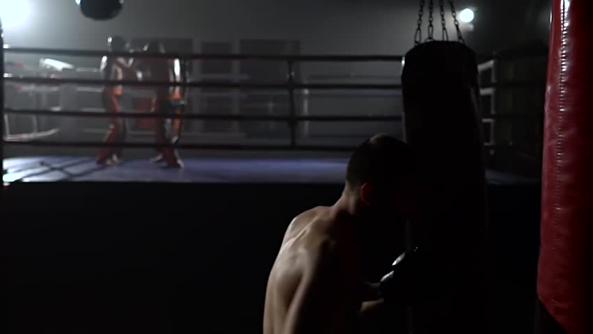 Men in gloves beats a pear, in the background in the ring there is a sparring of kickboxers. Slow motion