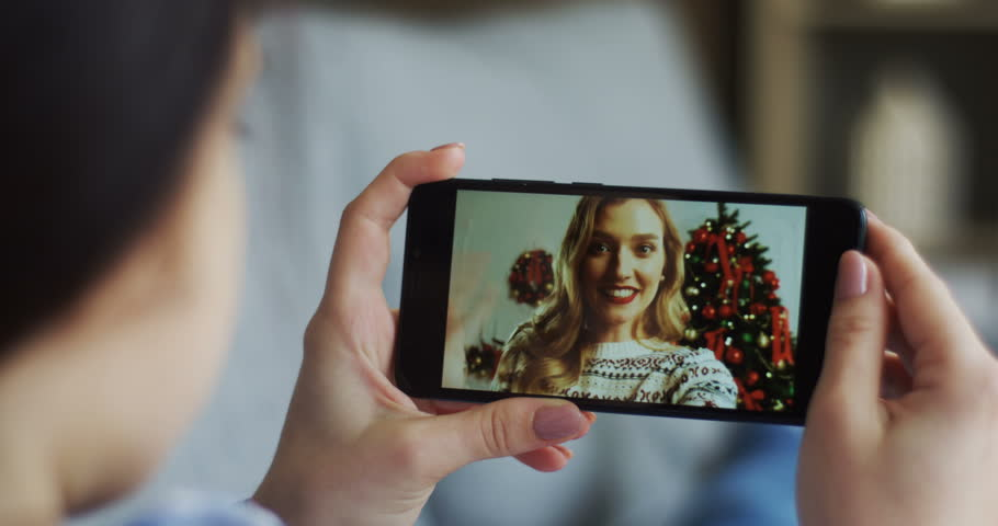 Close up of the black smartphone in hands of the young woman with beautiful blonde female friend near Christmas tree on the screen while having videochat. Rear.