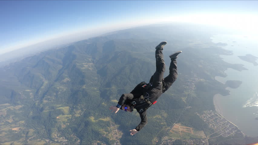 Skydiver having fun above the sea & mountains 4K | Shutterstock HD Video #1014204551