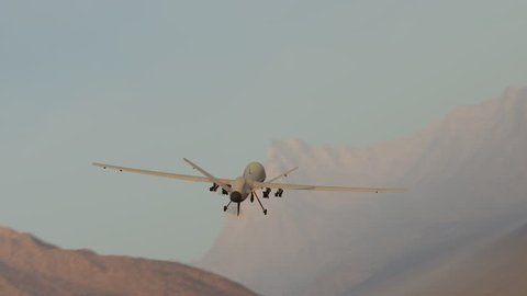 03592 Military predator drone flying over desert and mountains. Camera is fixed to drone.