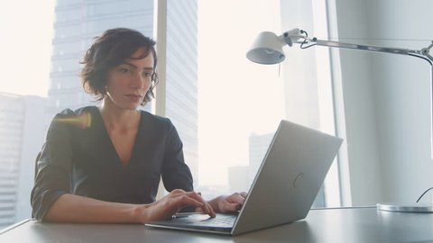 Confident Businesswoman Working on a Laptop in Her Modern Office. Stylish Beautiful Woman Doing Important Job. In the Window Big City Business District View.