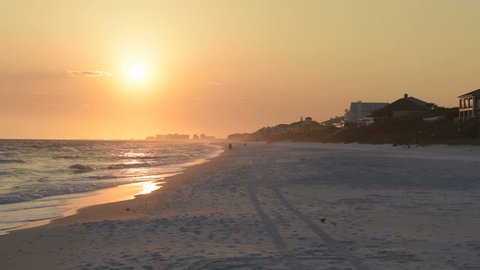 Dreamy pastel orange sunset in Santa Rosa Beach, Florida with Pensacola coastline coast cityscape skyline, houses, in panhandle with ocean gulf of mexico waves washing in slow motion