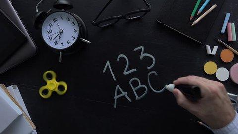 Teacher writing 123 ABC on school blackboard