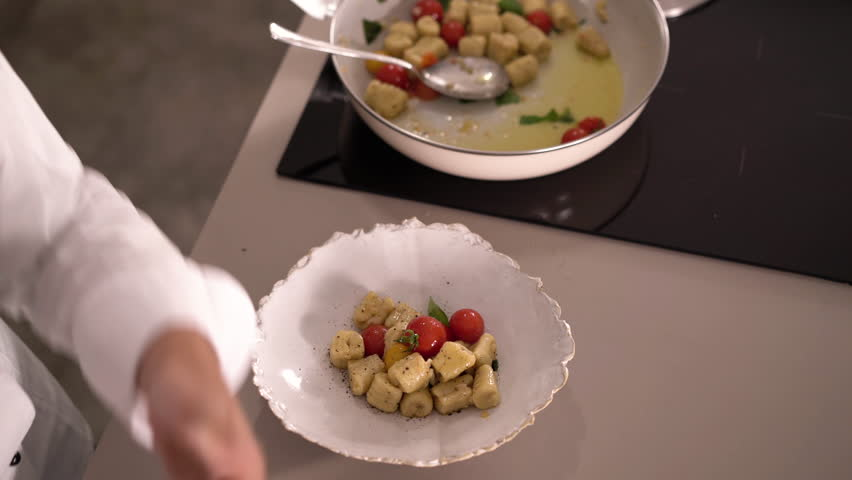 4K cooking footage, detail top view woman grating nutmeg over gnocchi with tomato and basil on plate beside induction cooktop with pan