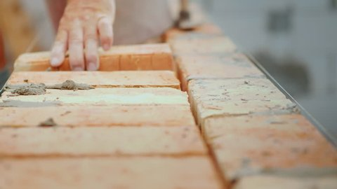 Workers laying brickwork. Manual work at the construction site