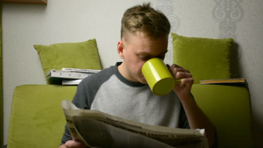 Spitting tea onto paper while reading fake news by young man indoors
