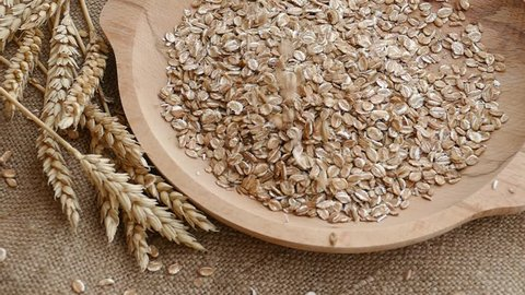 Ears of wheat and rye muesli falling into empty wooden plate,slow motion