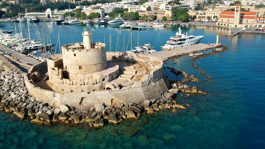 Aerial birds eye view drone video of Rhodes city island, Dodecanese, Greece. Panorama with Mandraki port, lagoon and clear blue water. Famous tourist destination in South Europe