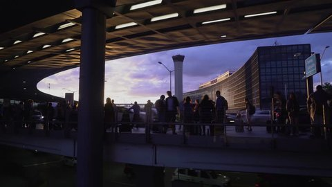 Chicago, Illinois / USA - July 26 2018: 4K Long exposure time lapse of travelers waiting at sunset outside Chicago O'Hare International Airport outside by Hilton waiting to be picked up at Terminal 3.