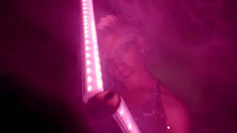 Alluring girl is moving in a nightclub in smoke, looking at camera. She is holding two pink elongated lamps and waving them