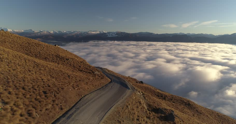 Aerial shot from a mountain over a sea of clouds with snow capped mountains in the background