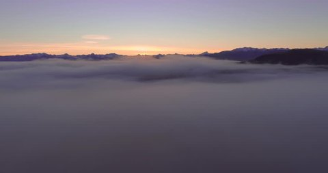 Aerial long pull back shot dipping into a sea of clouds in New Zealand