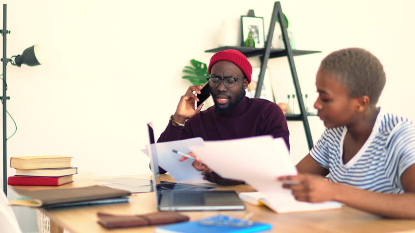 Dark skinned male and female colleagues concentrated on job in office using modern technologies and wifi, african american man making telephone call on work while his woman coworker typing on netbook