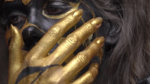 Shooting close-up, a woman in black gold makeup touches her face with her hands