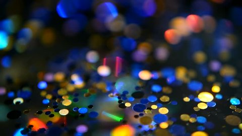 Defocused shimmering multicolored glitter confetti, black background. Party, magic, imagination. Rainbow colors, sparkle circles. Holiday abstract festive texture of shiny blurred bokeh light spots.