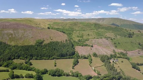 Aerial drone view flying over green fields and farmland in the Brecon Beacons, South Wales