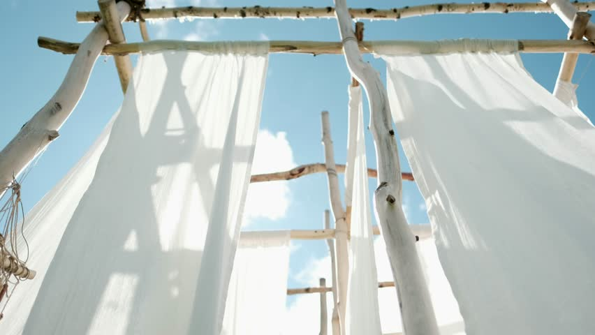 White linen cloth on wooden poles swings in the wind. Against the blue sky and green trees and fields. | Shutterstock HD Video #1014364001