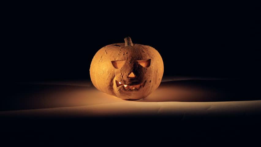 Illuminated carved traditional jack-o-lantern in a dark room. Halloween pumpkin in dark.