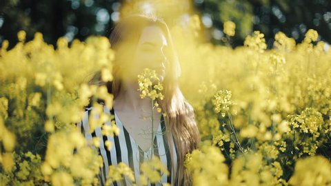 Pretty girl walks in the rape's field, posing, and smiling at camera. Beautiful young woman in the field of rape seed yellow flowers, sunny day