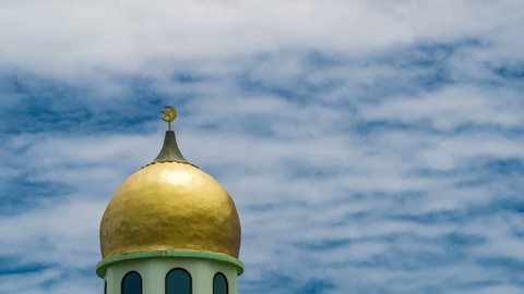 Timelapse of Golden Crescent Moon on Minaret of Islamic Mosque. Muslim Symbol at Day Blue Sky Background with Moving Clouds