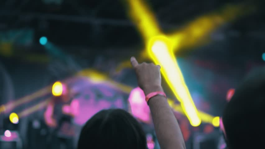 Night Rock Concert. People Cheer Move Lift and Clap Their Hands in Unison Against the Strobing Stage Lights. the hand close-up is directed upwards and shows the rock and roll sign. flicker of light
