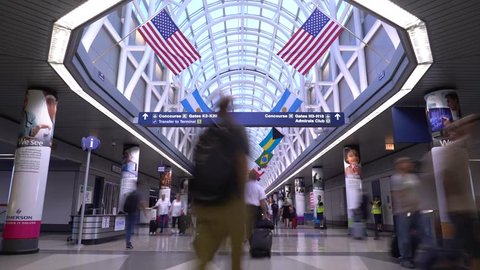 Chicago, Illinois / USA - July 26 2018: 4K 15 second long exposure time lapse of travelers rushing through Chicago O'Hare International Airport hallway with flags of various countries hanging.
