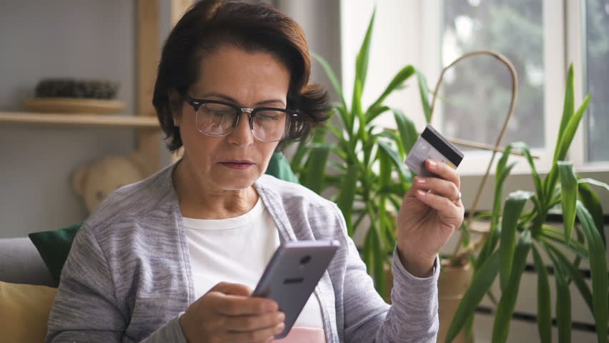 Mature woman in glasses paying for her online shopping with credit card, typing number to brand-new smartphone in her hand. Indoors. Portrait. | Shutterstock HD Video #1014410321