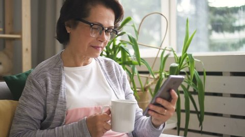 Beautiful mature woman in glasses drinking coffee from white mug, reading message on her smartphone and smiling being at home. Indoors. Portrait.