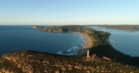 Barrenjoye Head Lighthouse on the top of headland sandstone rock in early morning warm light flying back above Palm beach and broken bay coast of Sydney.