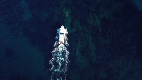 View from above, aerial view of a yacht sailing on a transparent and turquoise sea. Emerald Coast, Sardinia, Italy.