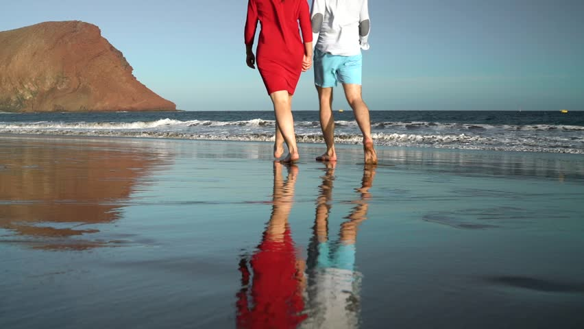 Couple in love carefree walking to the water on the beach. Picturesque ocean coast of Tenerife, Canarian Islands, Spain.
