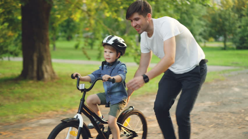 Handsome young man loving father is teaching his small son to ride bicycle in park on summer day, boy is riding bike while dad is holding him and running. | Shutterstock HD Video #1014435341
