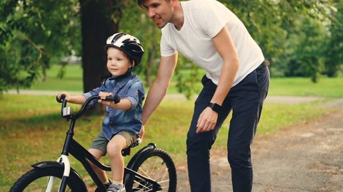 Slow motion of cheerful guy caring father teaching his small son to ride bicycle in park. Cute boy is cycling while young man is holding bike and helping child.