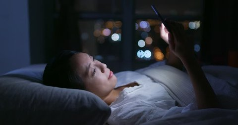 Woman use of mobile phone and lying on bed at night