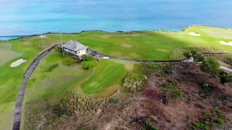 Aerial view of luxury golf field next the cliff, ocean and beach in Bali island, Indonesia.  Aerial view of footpath on golf course.