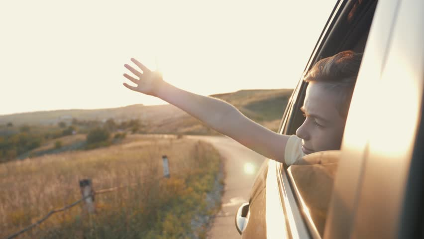 Teen boy looking out the car window and waving his hand. | Shutterstock HD Video #1014476471